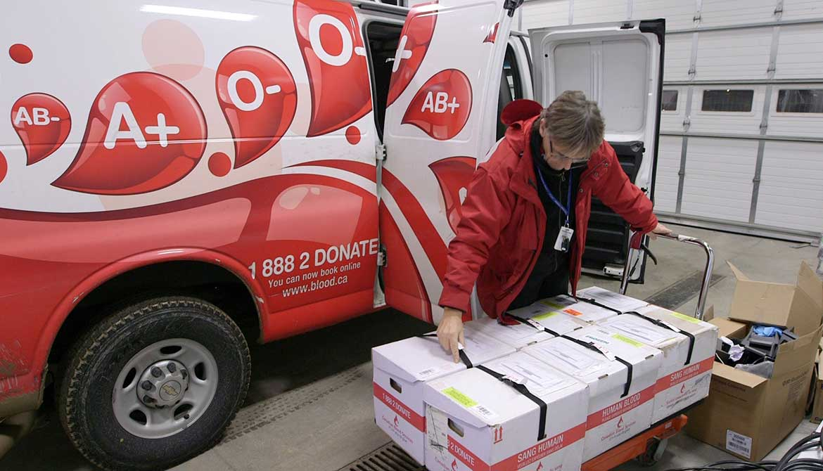 A worker from Canadian Blood Services loads a van with blood products.
