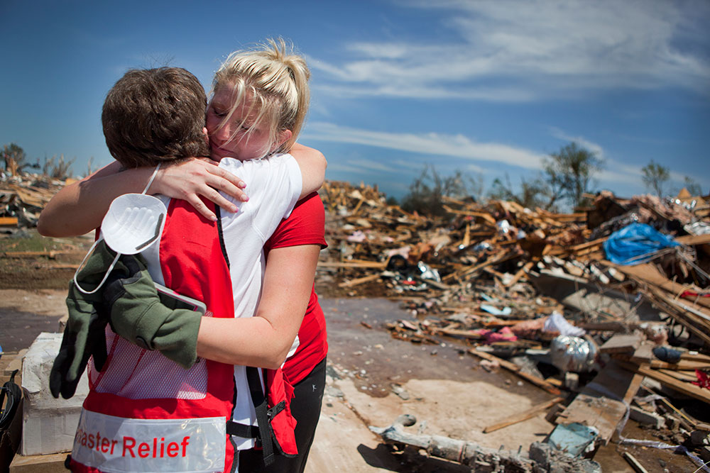 May 22, 2013. Moore, Oklahoma. Resident Ashley Sylvester awaits her husband's return from military service in Afghanistan while she cleans the remains of their home. After seeing a familiar face when Red Cross volunteers visited her neighborhood, Sylvester hugs her friend Harriet Wingo. Photo by Talia Frenkel/American Red Cross